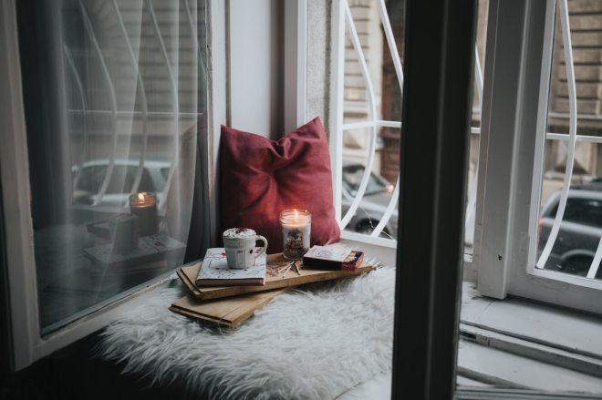 открытое окно, горит свеча, подушка и мягкий плед - хюгге атмосфера